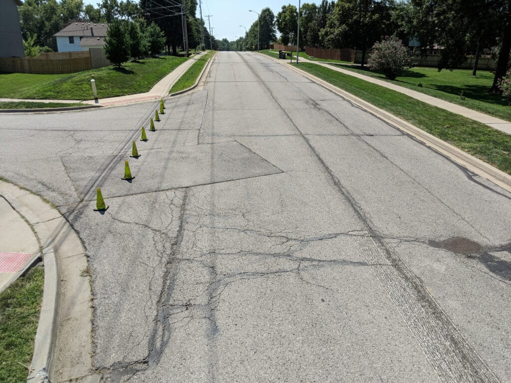 road with cracks and utility cuts with cones