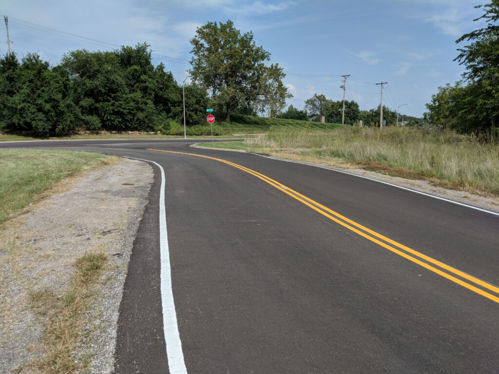 farm road with new driving surface yellow stripes white stripes and a stop sign