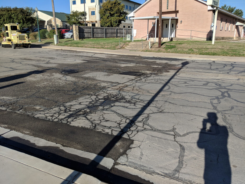 road with cracks and a yellow vehicle parked in the street
