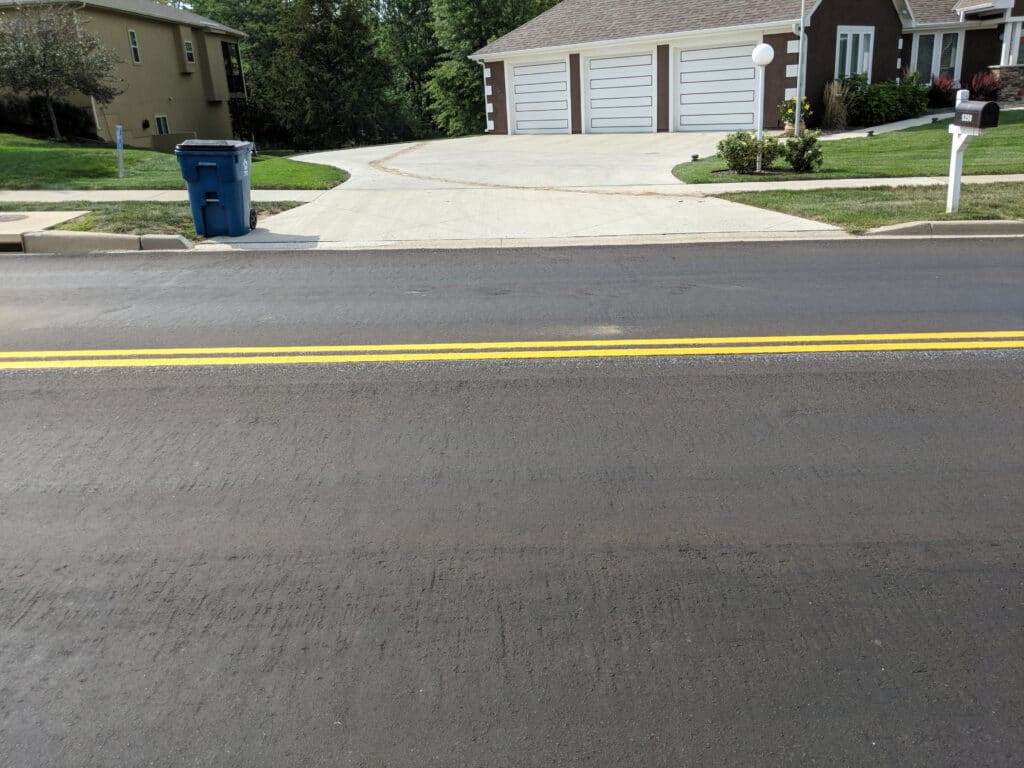 paved residential street with double yellow solid stripes in front of 3 car garage home