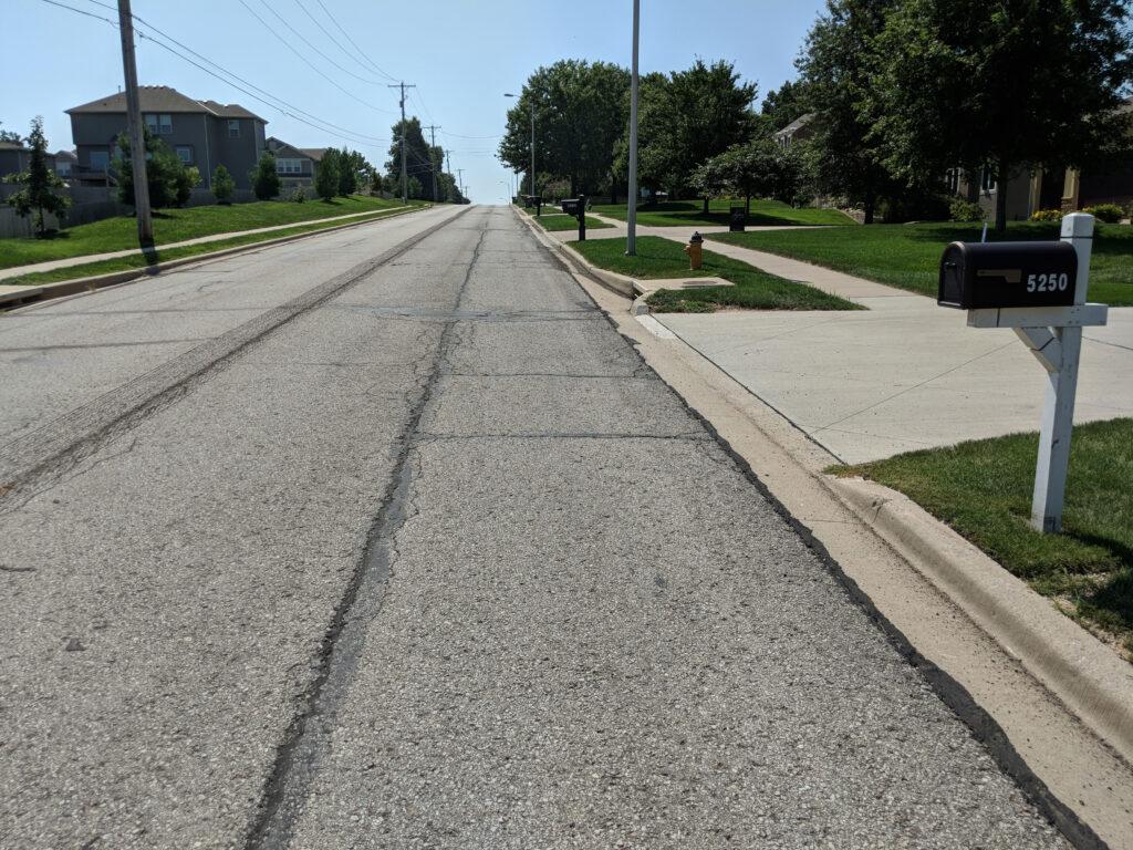 neighborhood street with mailbox next to a driveway