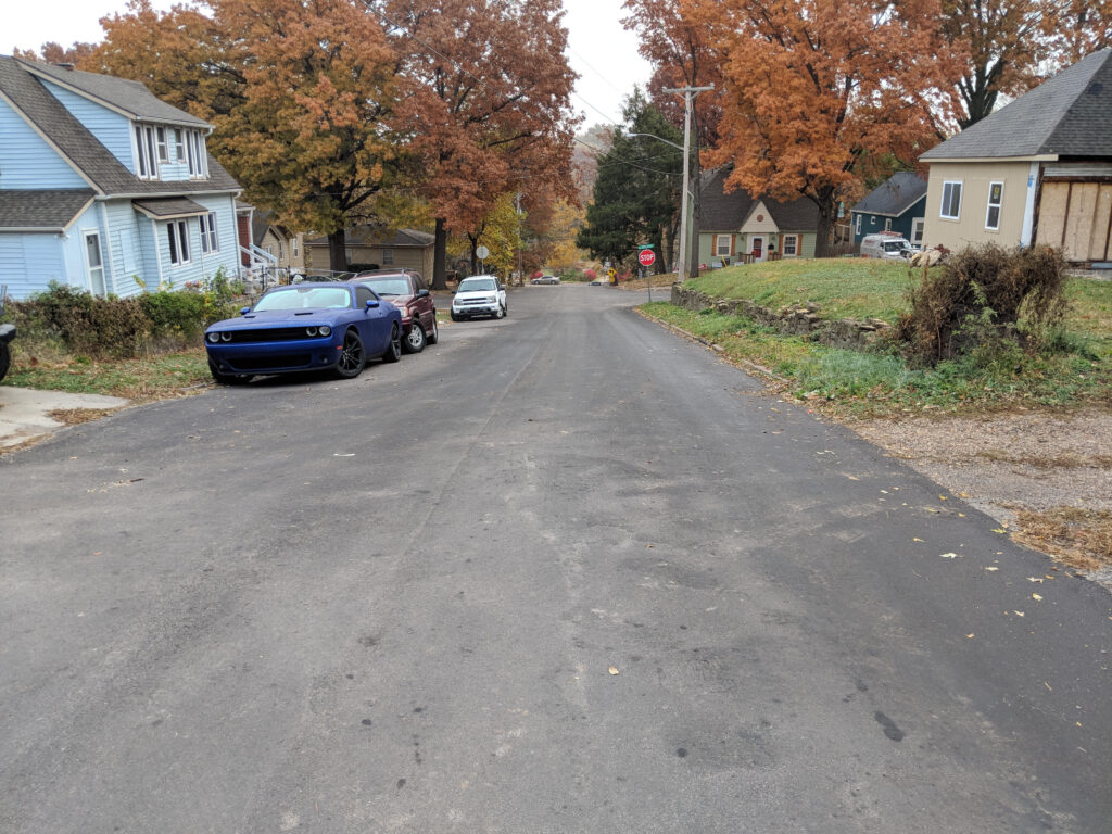 paved road with two cars pulled of to the side of the road in front of a house
