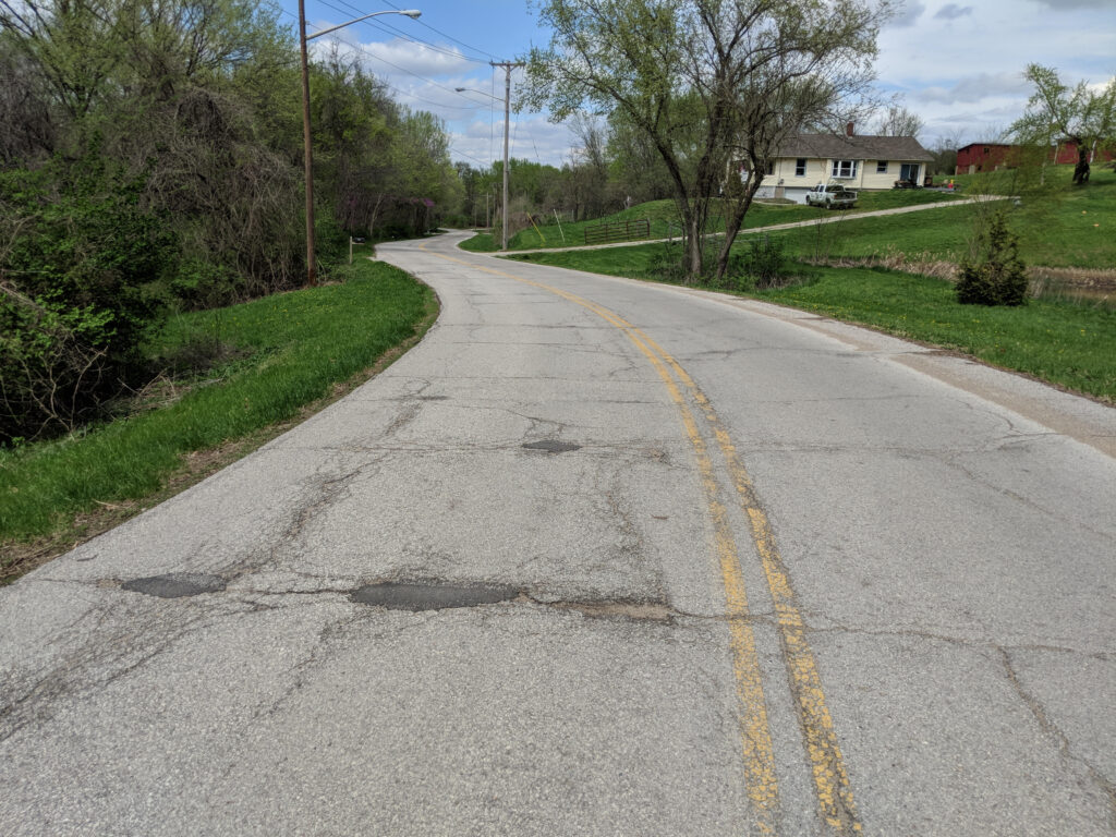 old beat up road with faded double yellow line in the middle